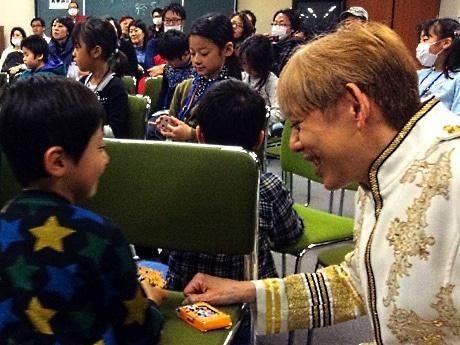 タジマジックさんにマジックの手ほどきを受ける児童