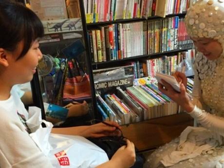 似顔絵を描いてもらった参加者と「えびずし」の衣装でイラストを描く杉浦さん(右)