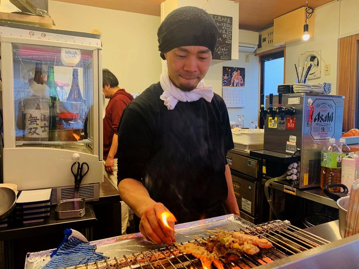 焼き鳥を焼く店主の中山貴史さんと店内