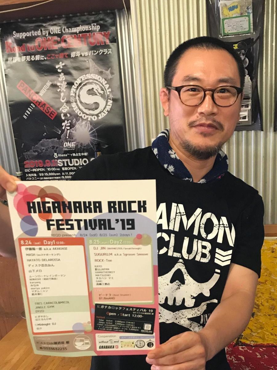 「ヒガナカロックフェスティバル」ポスターを持つ店主の高橋幸人さん