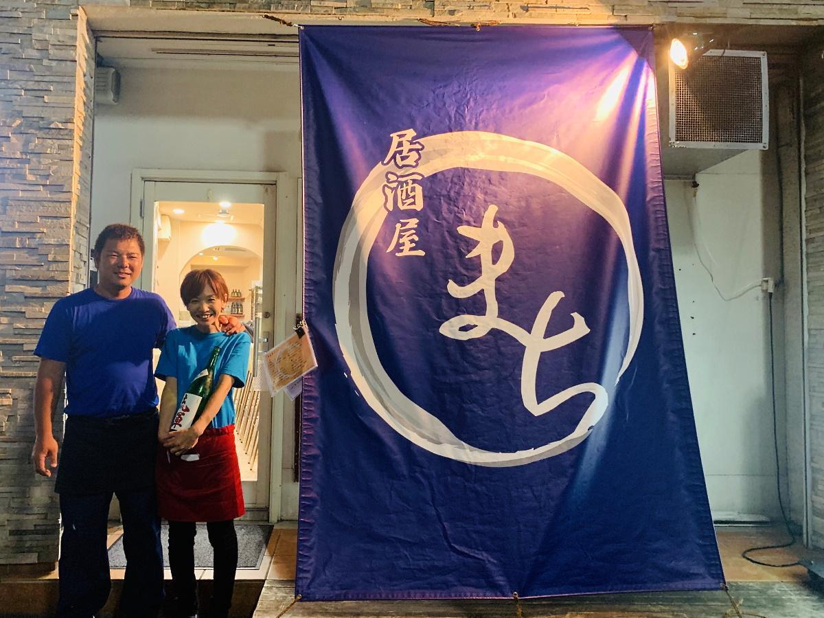 店主の町亮輔さん(左)、おかみの瞳さん夫妻と「居酒屋まち」外観