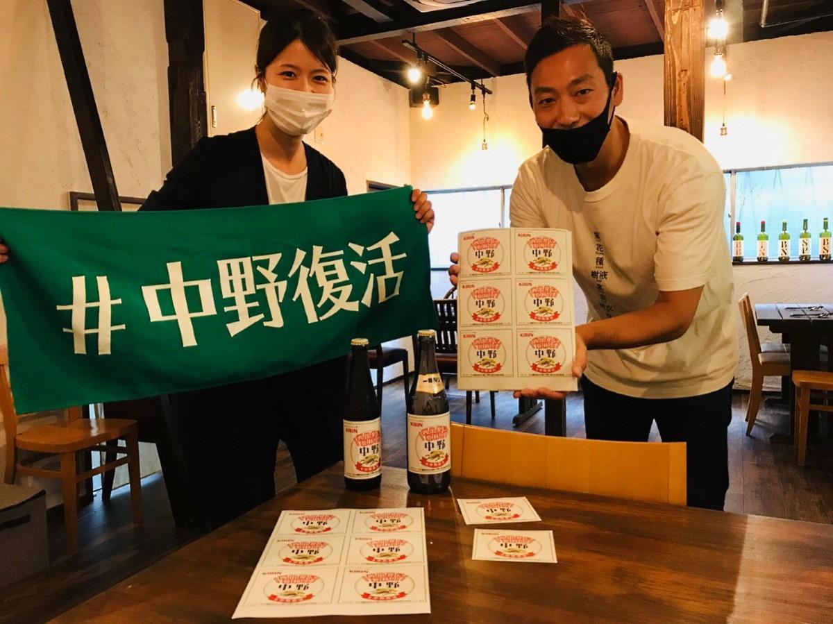 キリンビール中野エリア担当(左)、ロジ店主の蟻塚純さん(右)と「再出発に乾杯」ステッカー