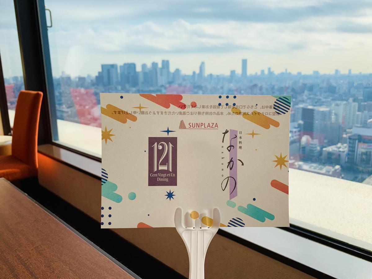 日本料理「なかの」とレストラン「121ダイニング」の名前が入った飛沫防止用手持ちシールド