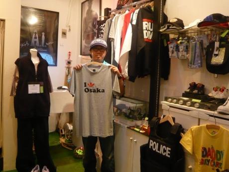 店主の吉田聡さんが手に持つのは、世界で100枚限定だというアディダスのTシャツ。大阪でしか手に入らないアイテム