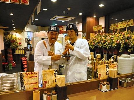 上山会長(左)と藪口店長(右)。赤井英和さんから贈られたという「会長」人形とともに