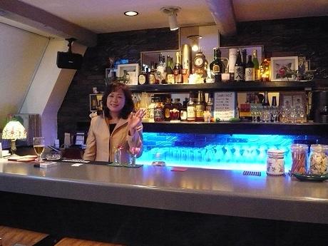 念願のバーをオープンし、笑顔で客を迎える恵美子さん