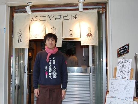 「売上げアップ」目指し奮闘する塩崎雄一郎さん。自作トレーナーを着用