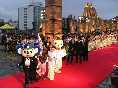 「ドアラ」や「フェレット」とともにレッドカーペットを歩く「くいだおれ太郎」とおかみさん(写真=シブヤ経済新聞)。