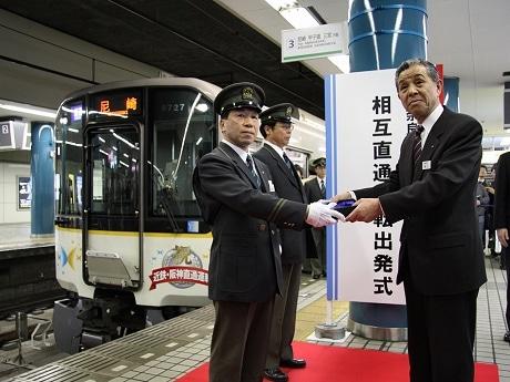 大阪難波駅発の一番列車の運転士に記念品を贈呈する野口満彦副社長(写真右)