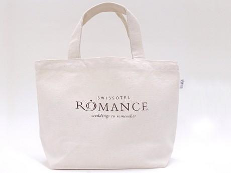 「ROMANCE」のロゴを配したエコバッグを女性社員が通勤に使用する