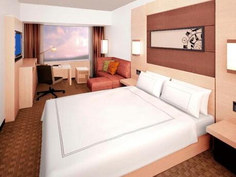 ベッド上のアートワークとソファのクッションには大阪と日本をモチーフにした図柄を入れる