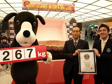 虹のまち商店街振興組合理事長・小儀俊光さん(写真中央)とギネス公式認定員(右)、なんばウォークマスコットの「なんばワン」