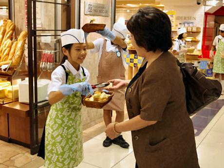 客にパンの試食を勧める児童
