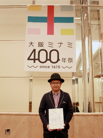 「大阪ミナミ400年祭」のロゴマークの最優秀賞に選ばれたデザイナーのクリオカイチロウさん