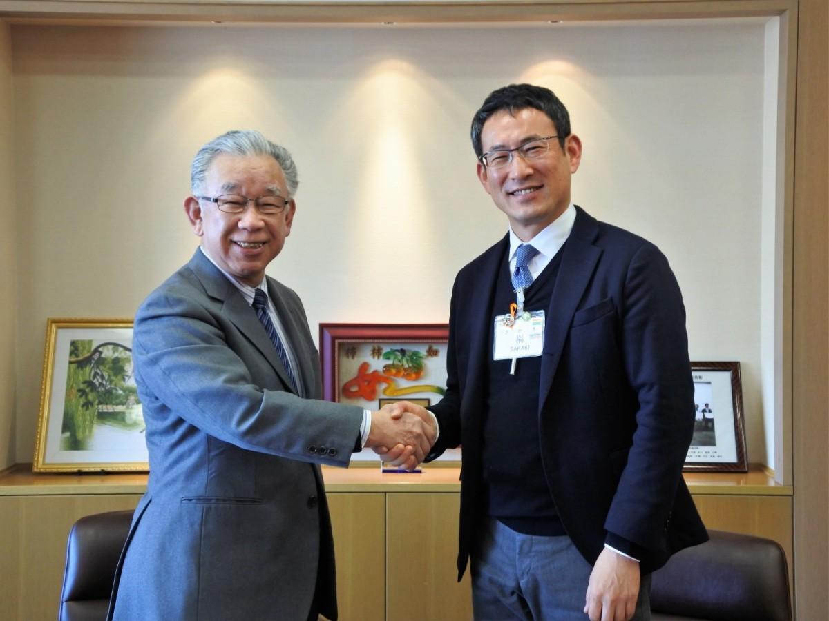 笑顔で握手をかわす長谷川理事長(左)と榊区長(右)