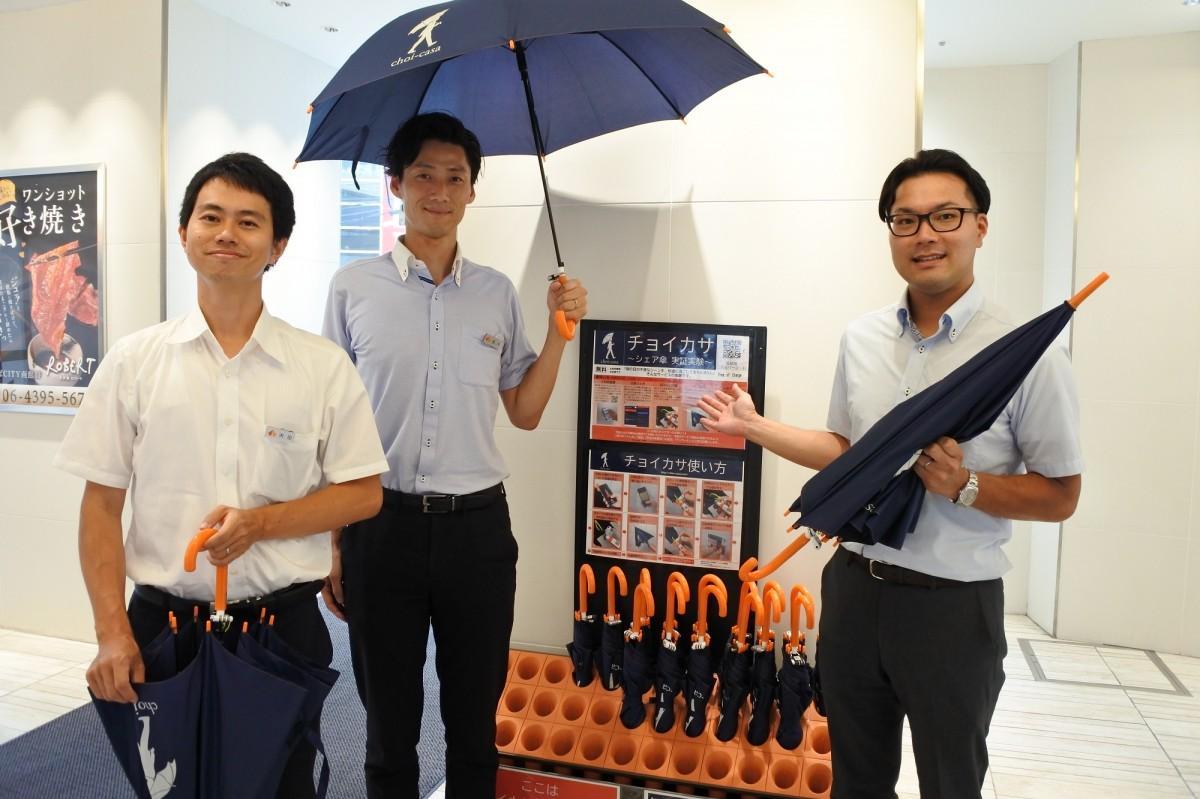 「チョイカサ」を考案した、グレーターなんば創造室の福井良佑さん(中)。傘に描かれたロゴマークも自らデザインした