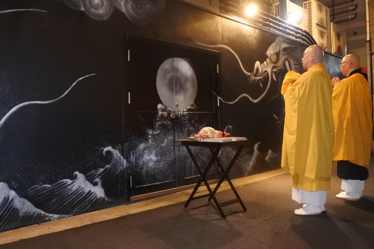 壁画の前で法要を執り行う鳥居弘昌住職