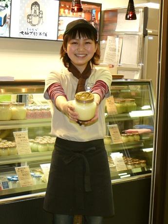 「大仏プリン」カスタード味の大サイズをアピールするスタッフ、近鉄奈良駅内「Meets Sweets」奈良店で