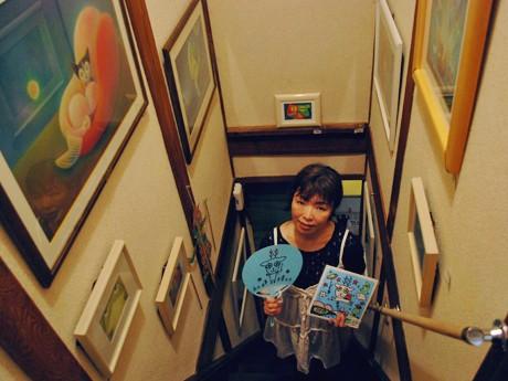 ギャラリー「五想庵」の階段でオリジナルキャラ「しくる」のグッズを手にした「5*SEASON」と大八木恵子さん
