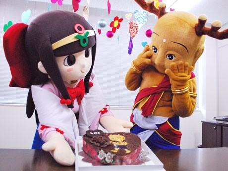 恋人候補の葛城市のマスコットキャラクター「蓮花ちゃん」から誕生日ケーキを受け取る「せんとくん」