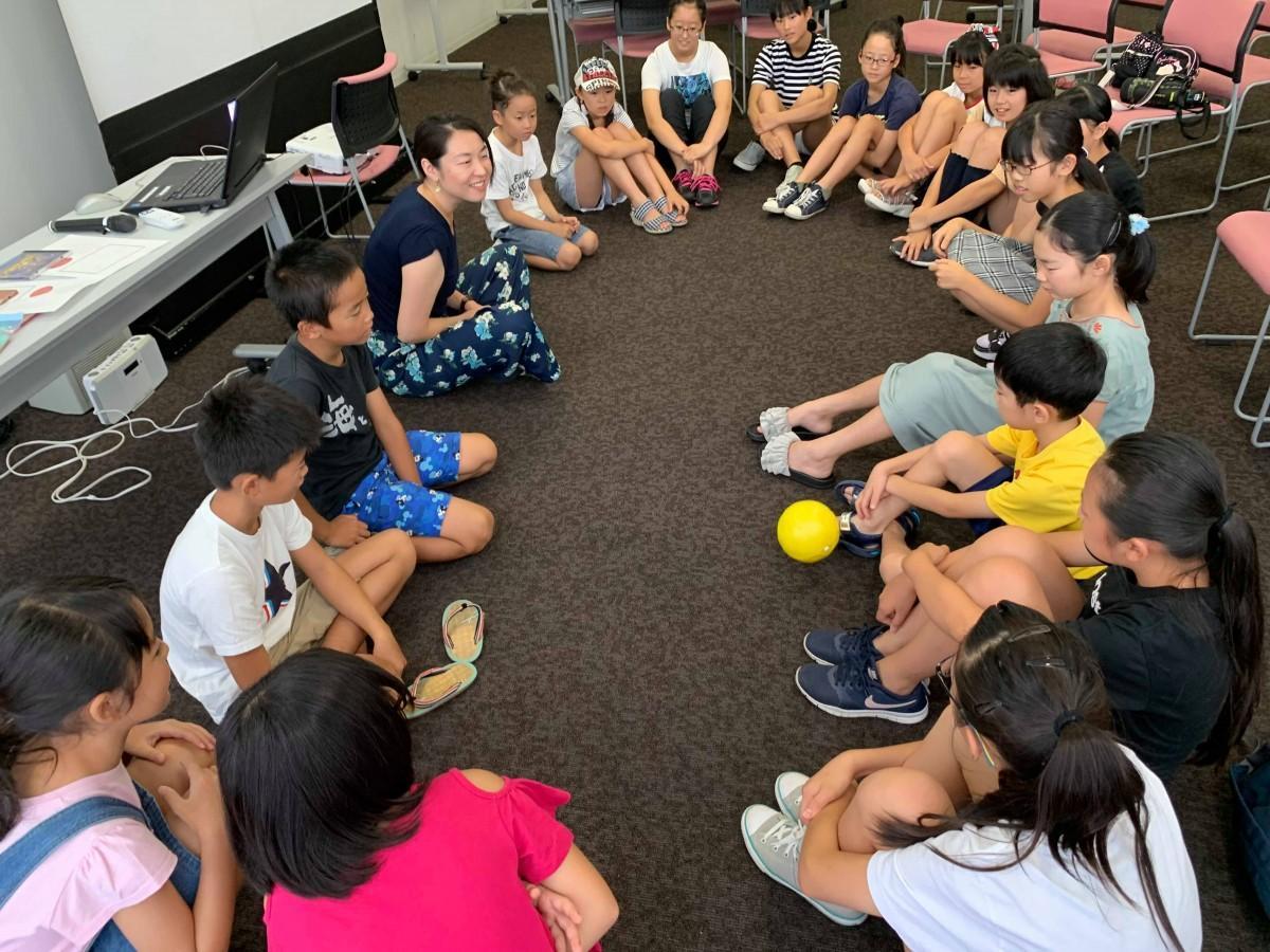 輪になり、ボールでコミュニケーションを取る参加者と講師