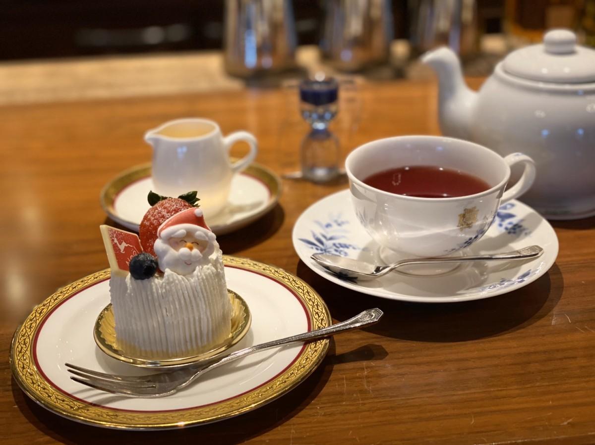 ケーキ「ミニ ノエル」と、ポットで提供されるドイツ・ロンネフェルト社の「グリューワインティー」。好みの甘さに調節できる「バニラシロップ」と、飲み頃を知らせるオイルタイマーが添えられる。