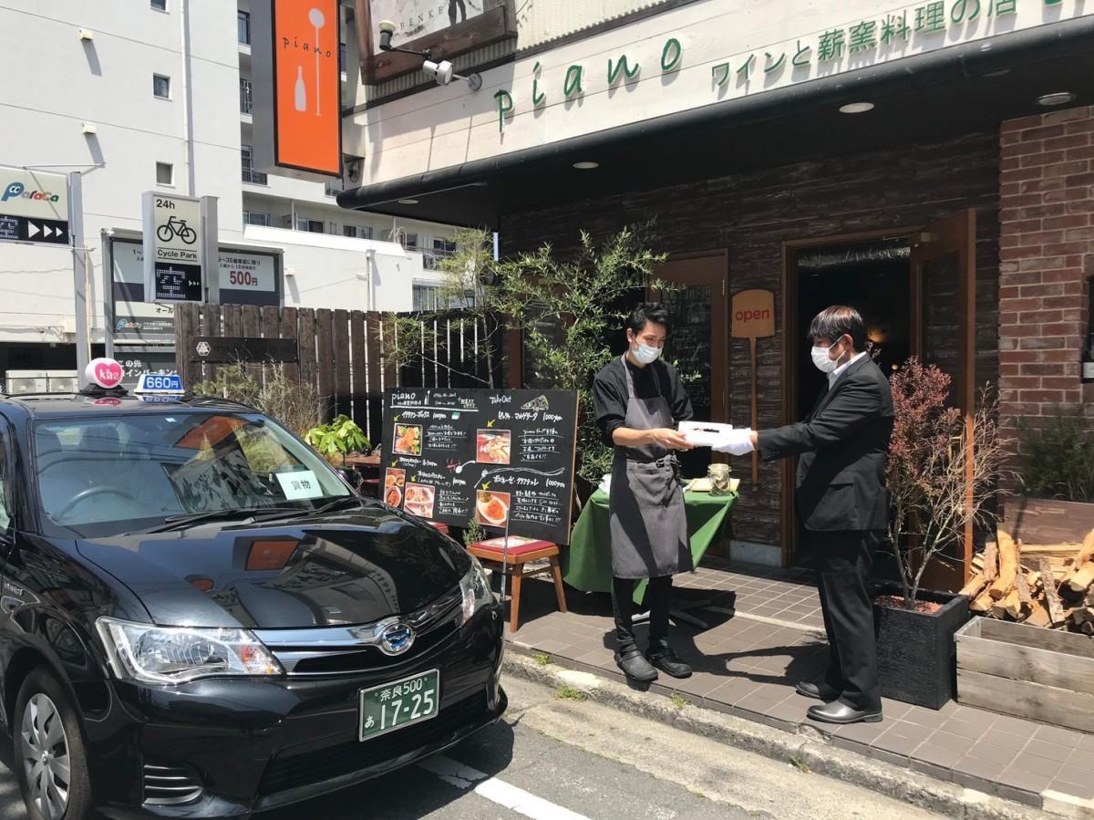 「男前タクシー」の運転手が提携店からテークアウト商品を受け取る様子