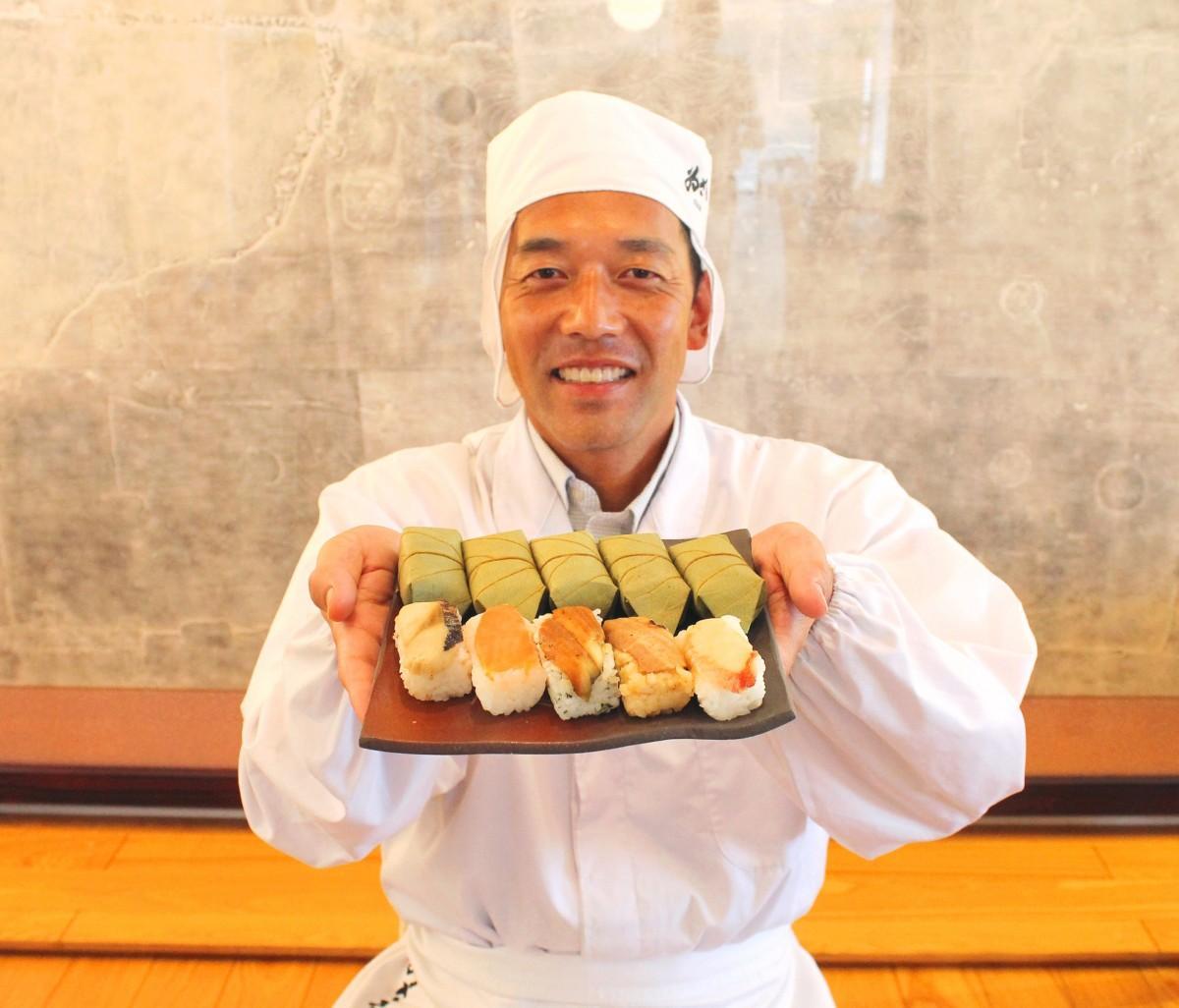 電子レンジで加熱し温めた「蒸し柿の葉寿司」を持つ販売部門の澤田さん