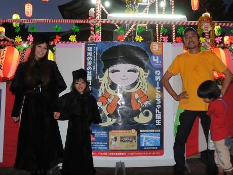 「ゆめーてるちゃん」のイラストと貫井武彦会長(右)。「メーテル」「ゆめーてるちゃん」のコスプレも