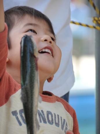 ニジマスを釣り上げ喜ぶ子ども