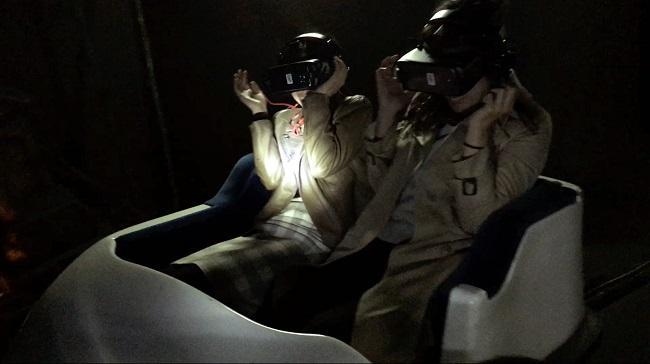 VRゴーグルとヘッドホンをつけライドに乗り込む「怨霊廃線VR」