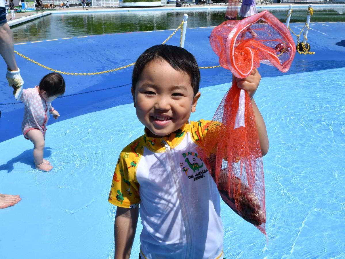 捕まえた魚に笑顔の子ども