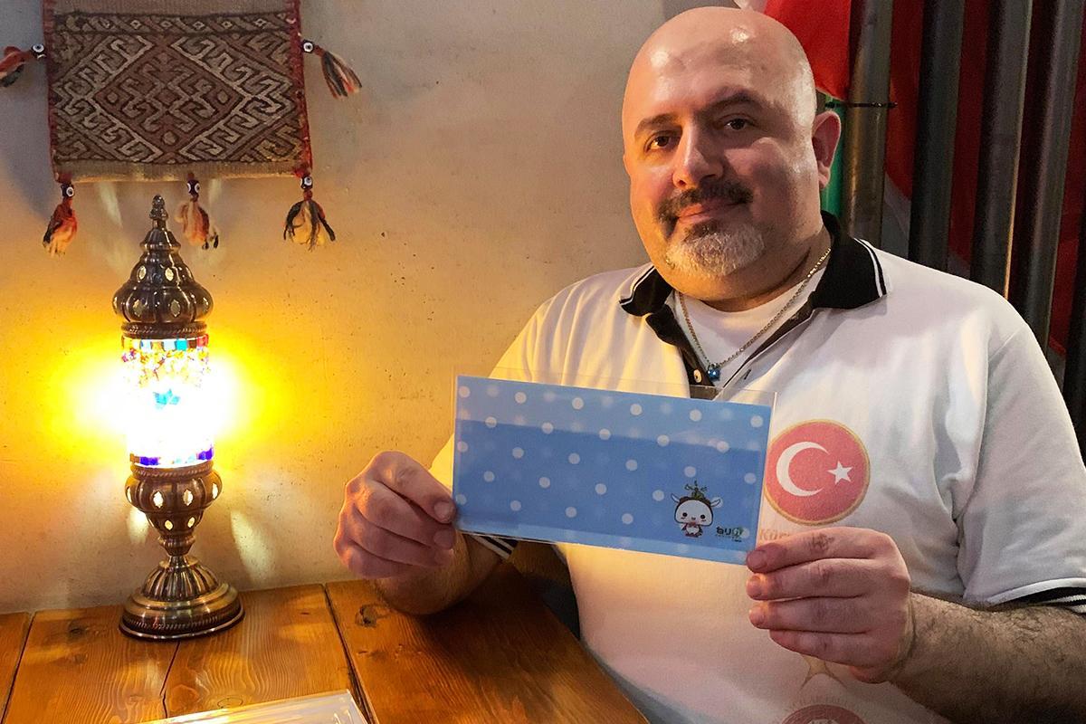 ねり丸マスクケースを持つトルコ料理店「ドルジャマフセン」のオーナーシェフ ウズンさん