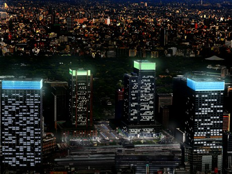 超高層ビルの頂部が青色(地球)と緑色(環境)にライトアップされる