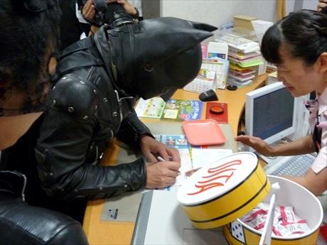 女子行員の指示の元、「だいぎん震災義援募金 大分県口」宛の送金伝票に記入するバッタモン