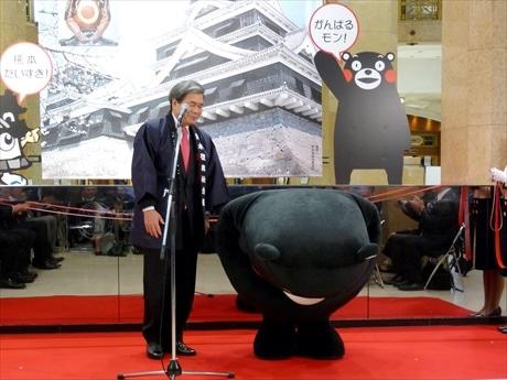 全国からの応援に、最敬礼するくまモン。左は浦島郁夫熊本県知事