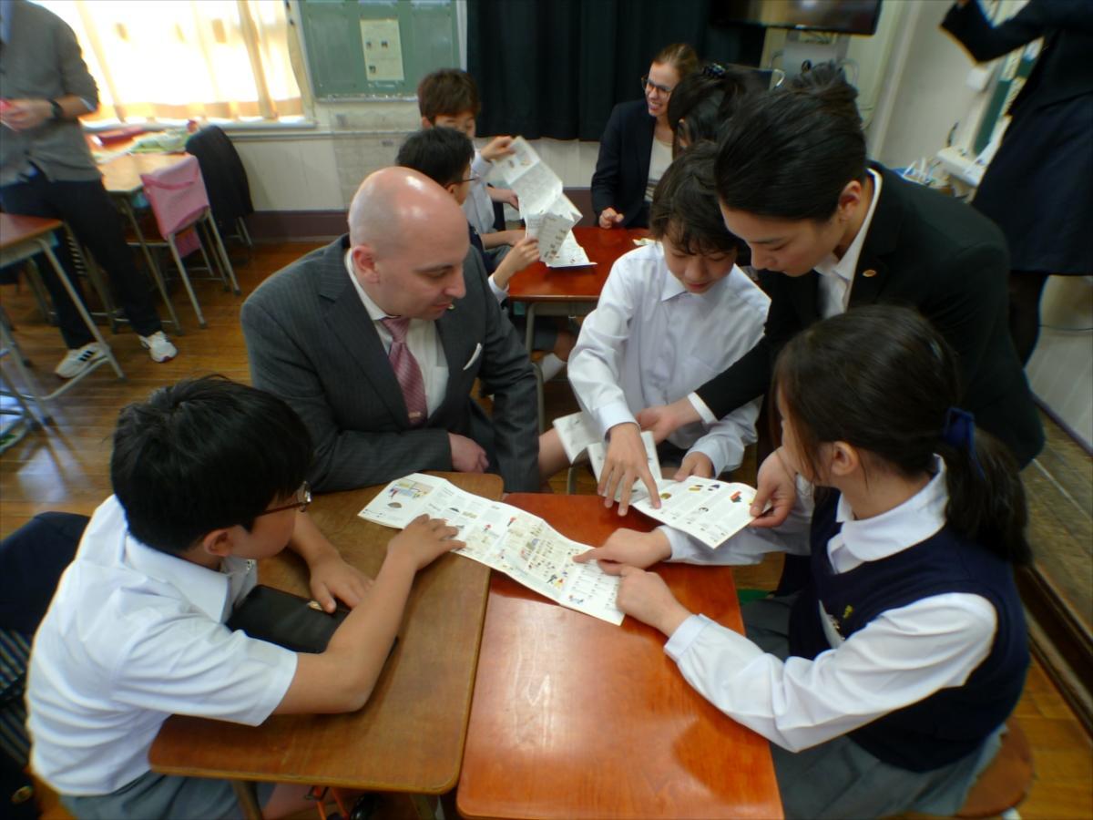「マンダリン オリエンタル 東京」が制作した「日本橋ガイド英語版」を使い、英語で地域を説明する児童ら