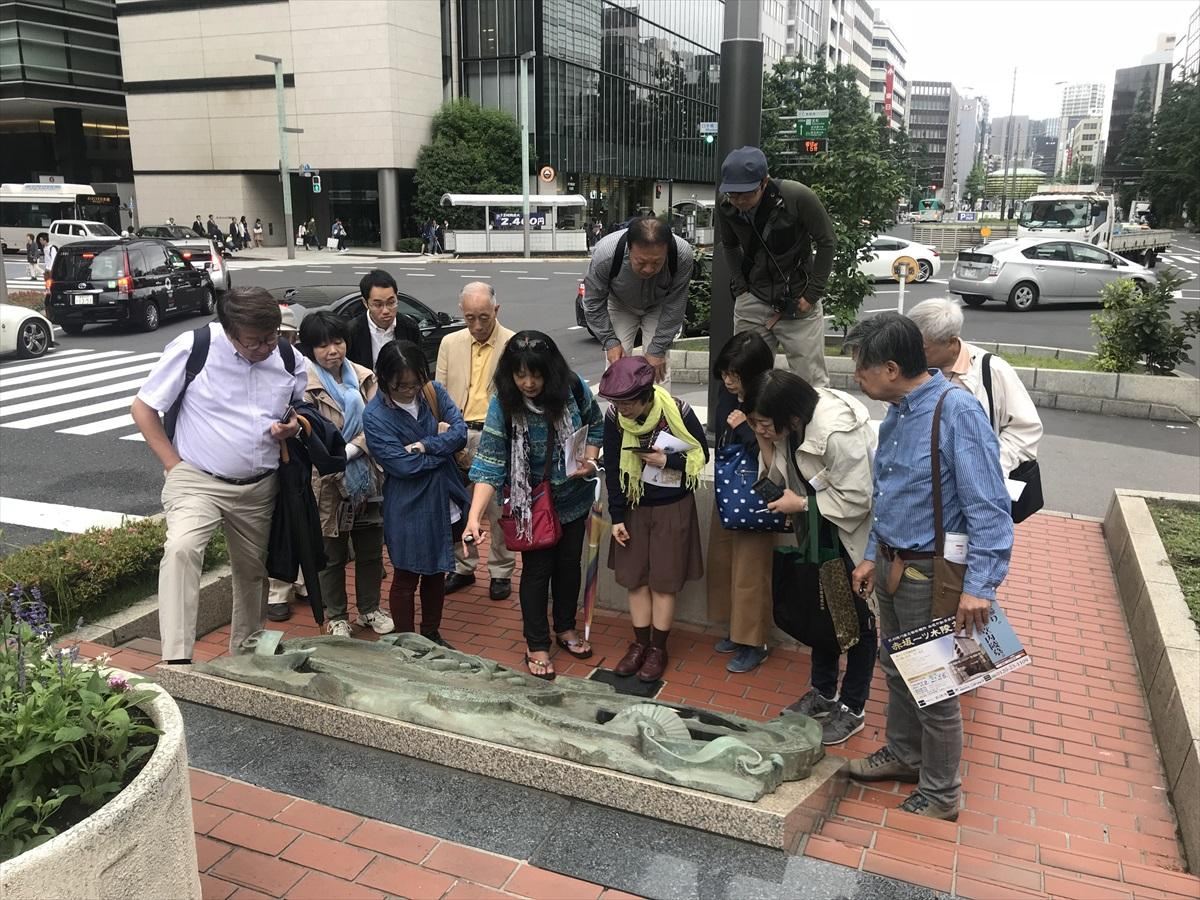 八重洲通りの中央分離帯にあるヤンヨーステンの記念碑を見学する参加者たち