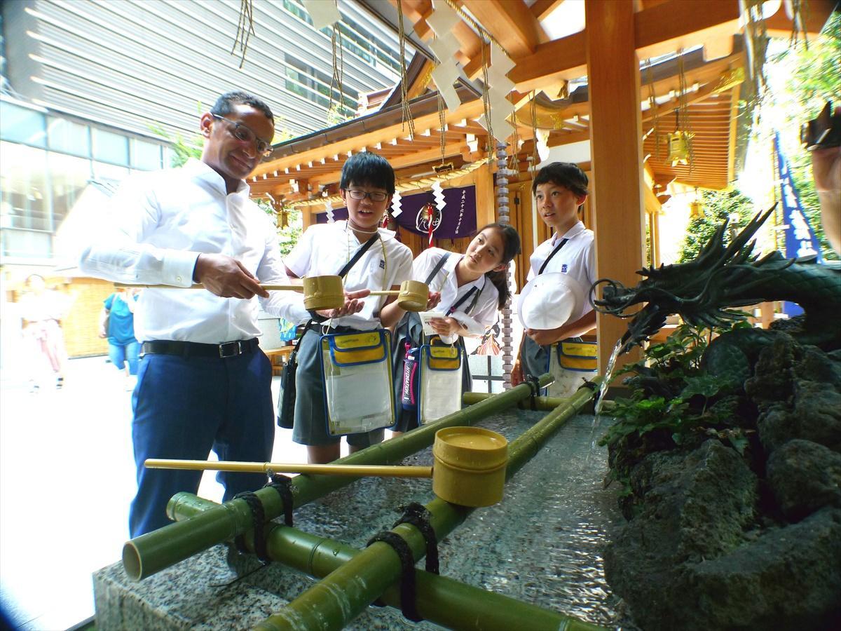 日本橋の福徳神社で手水の作法を英語で説明する児童たち