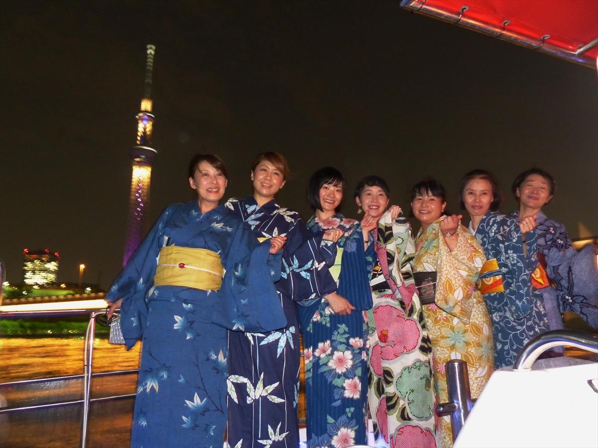 船上から東京スカイツリーと記念撮影する浴衣姿の女性客