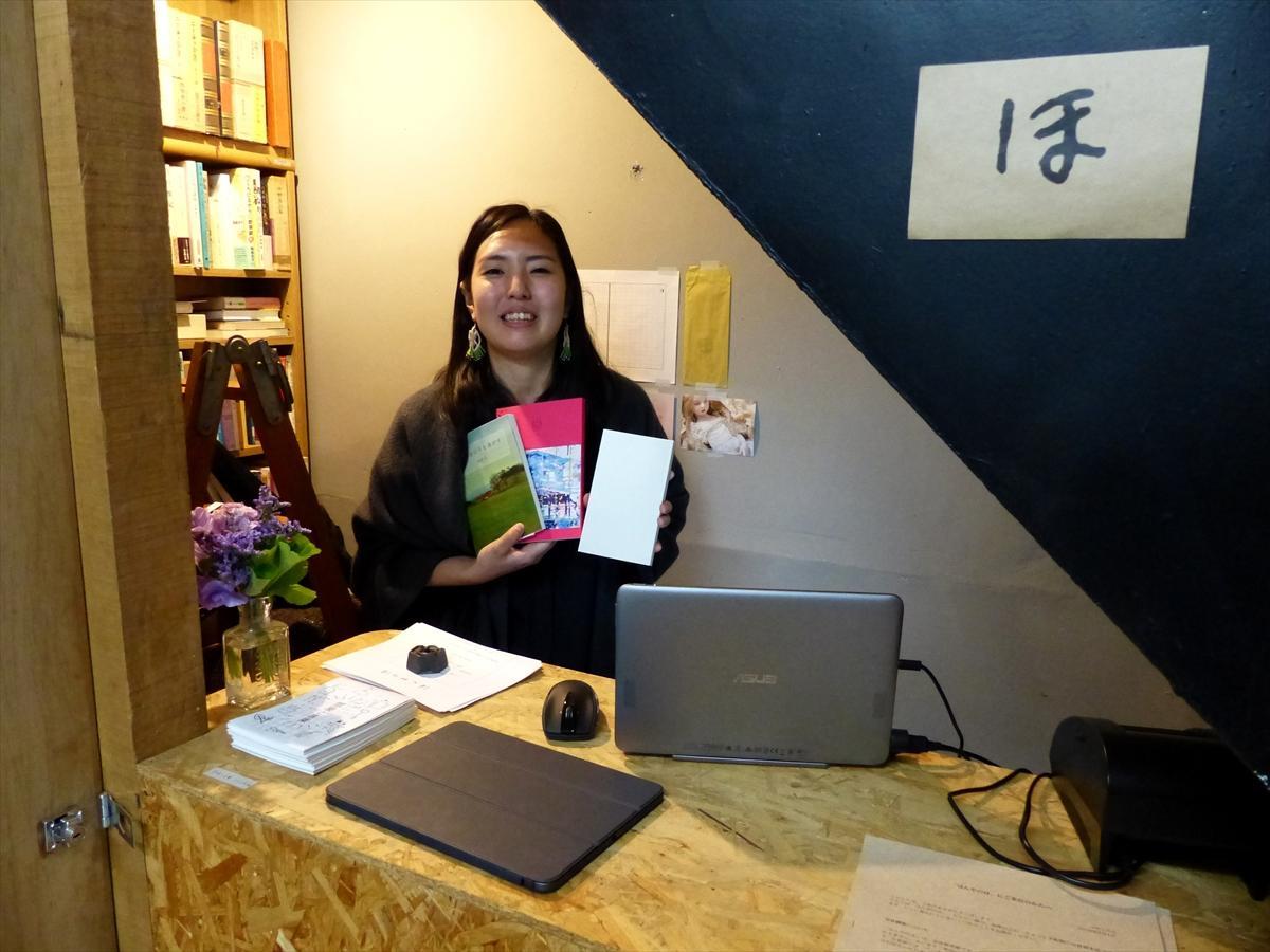 お気に入りの本を持つ店長の伊川佐保子さん。左奥の棚は「まだ売る決心がついていない」コーナー