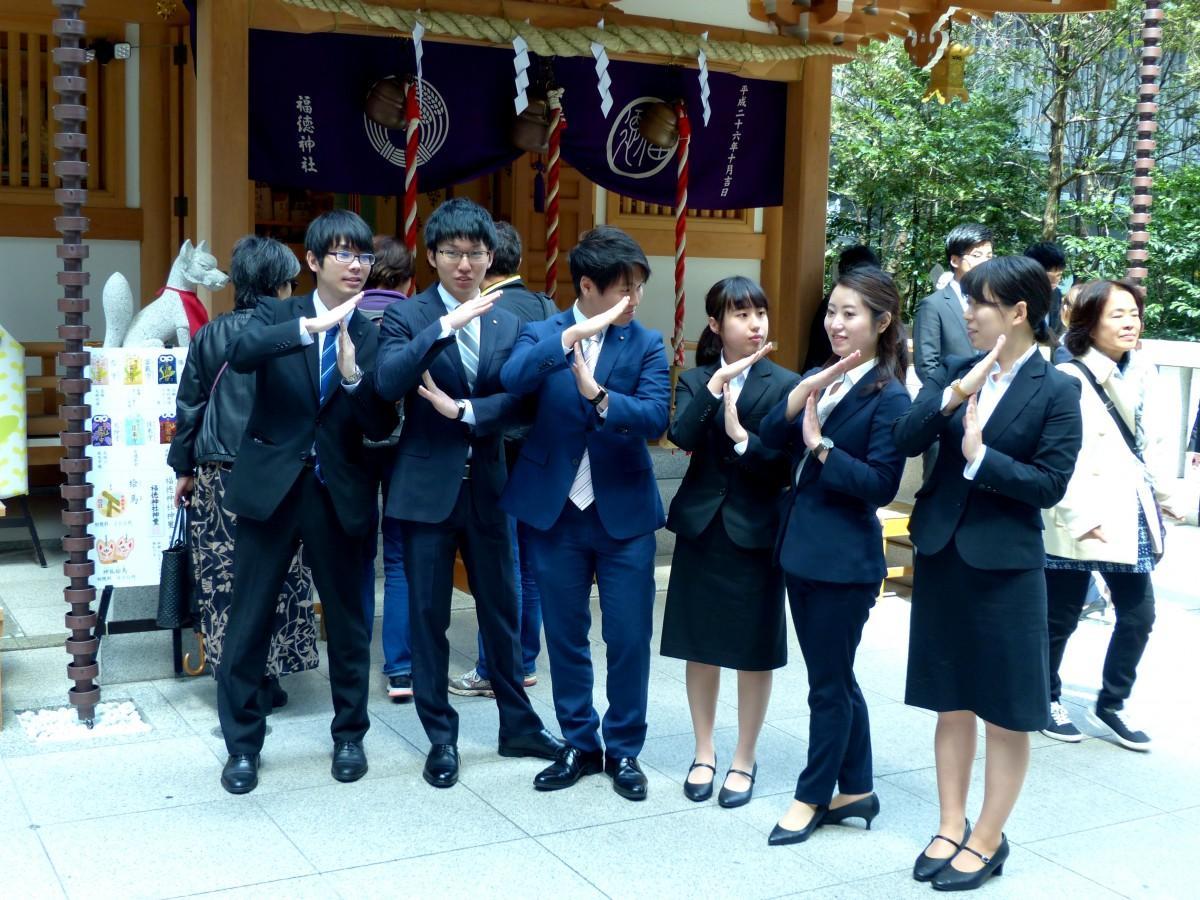 福徳神社参拝後、記念撮影する「にんべん」の新入社員たち。「にんべん」サインも練習中