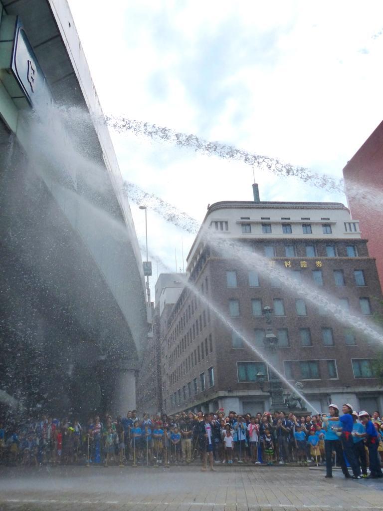 首都高に架かる日本橋の銘版にむけて、子ども消防団員らがホースを抱えながら放水