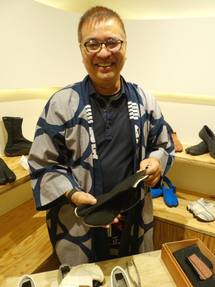 金栗四三モデルのレプリカを持つ地下足袋職人山中薫さん。大河ドラマ「いだてん」で足袋型シューズ製造シーンの指導も行った