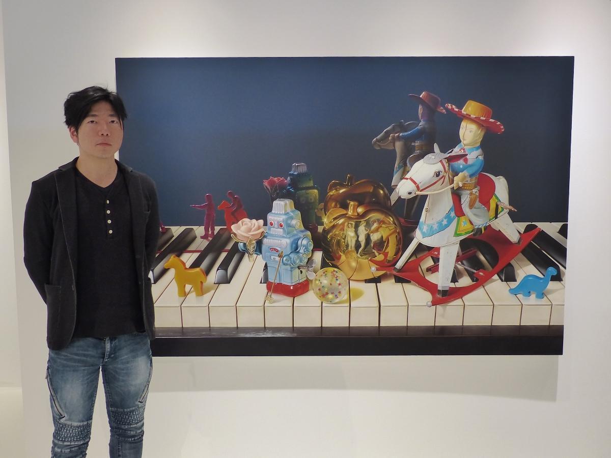 120号の大作「黄金のリンゴ」の前で、独自の世界観を語る戸泉恵徳さん