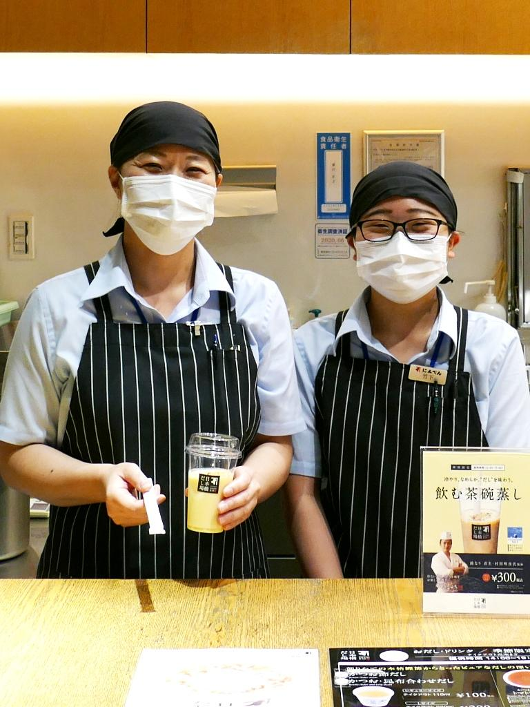 夏季限定商品の冷製ドリンク「飲む茶碗蒸し」を手にする店舗スタッフ