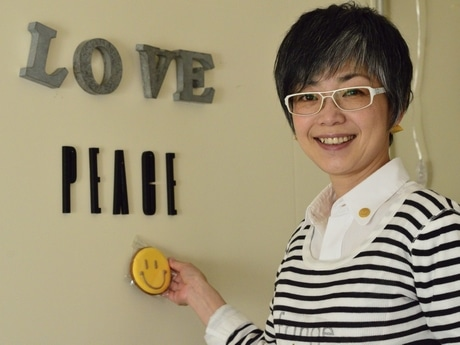 同店のテーマである「Love, Peace & Smile」の壁飾りの前に立つ店主の福永麻子さん