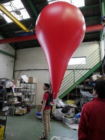 赤い大きな「バルーン」を背負ったパフォーマー(リハーサルの様子)