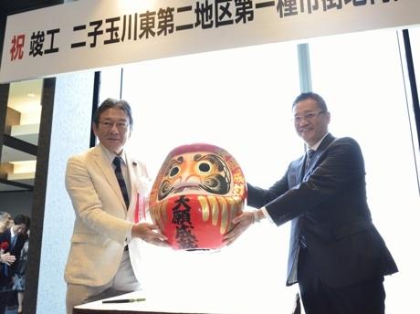 竣工披露会でだるまに目を入れた川邉組合理事長(左)