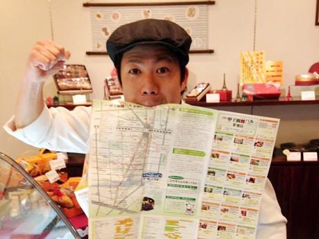 バルマップをくわえガッツポーズする実行委員長の青木さん